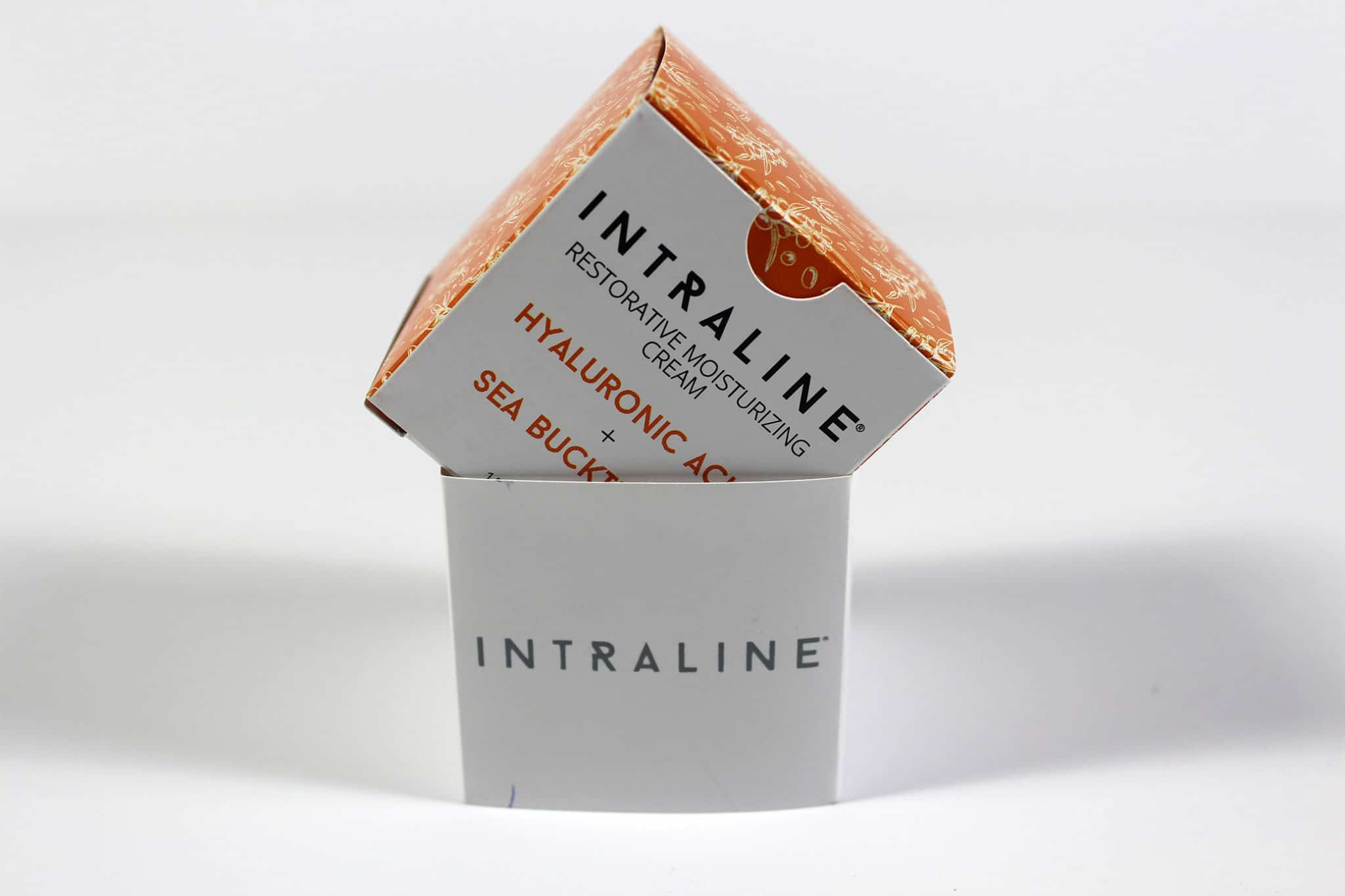 Colourful printed cosmetic packaging box for Intraline sitting at an angle on top of the outer sleeve