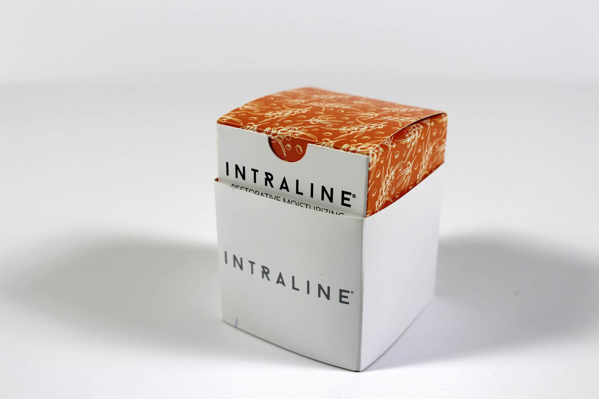 Colourful printed cosmetic packaging box for Intraline with outer sleeve wrapped round it