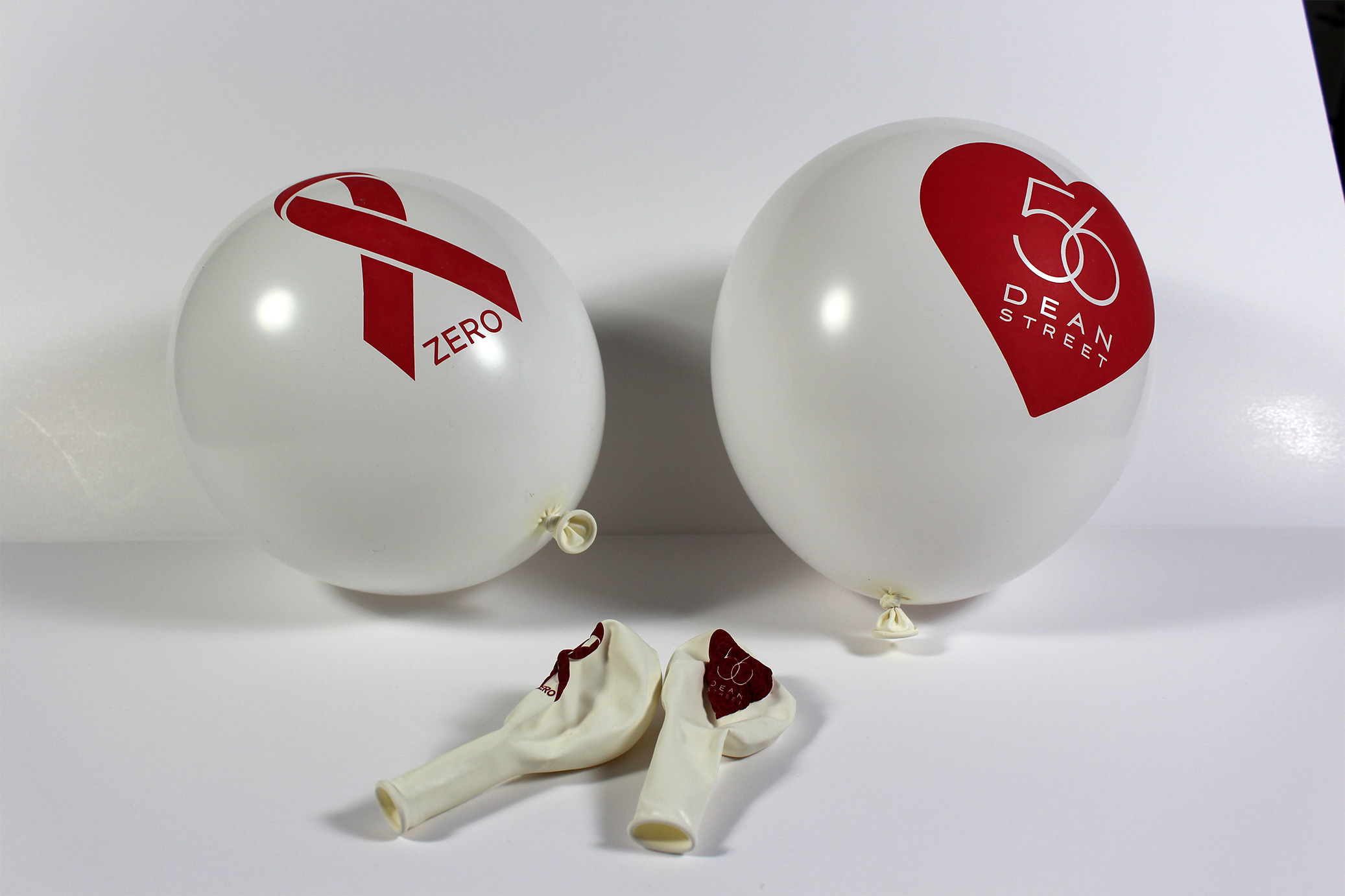 Four white balloons with red print, two inflated, two deflated for Dean Street
