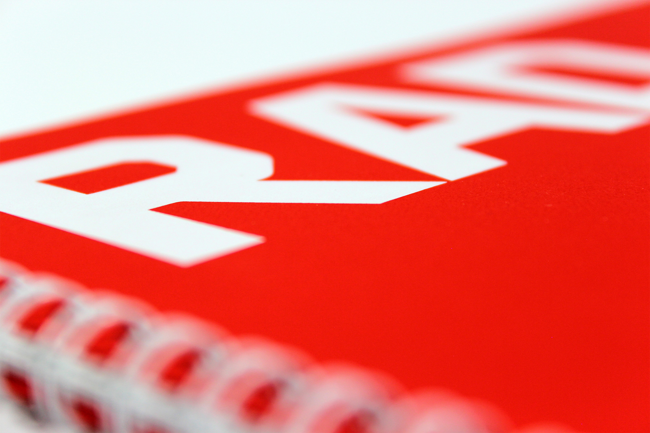 Printed Wiro-bound corporate promotional brochure for RAD - close-up showing the binding and red card front cover with spot white printed text