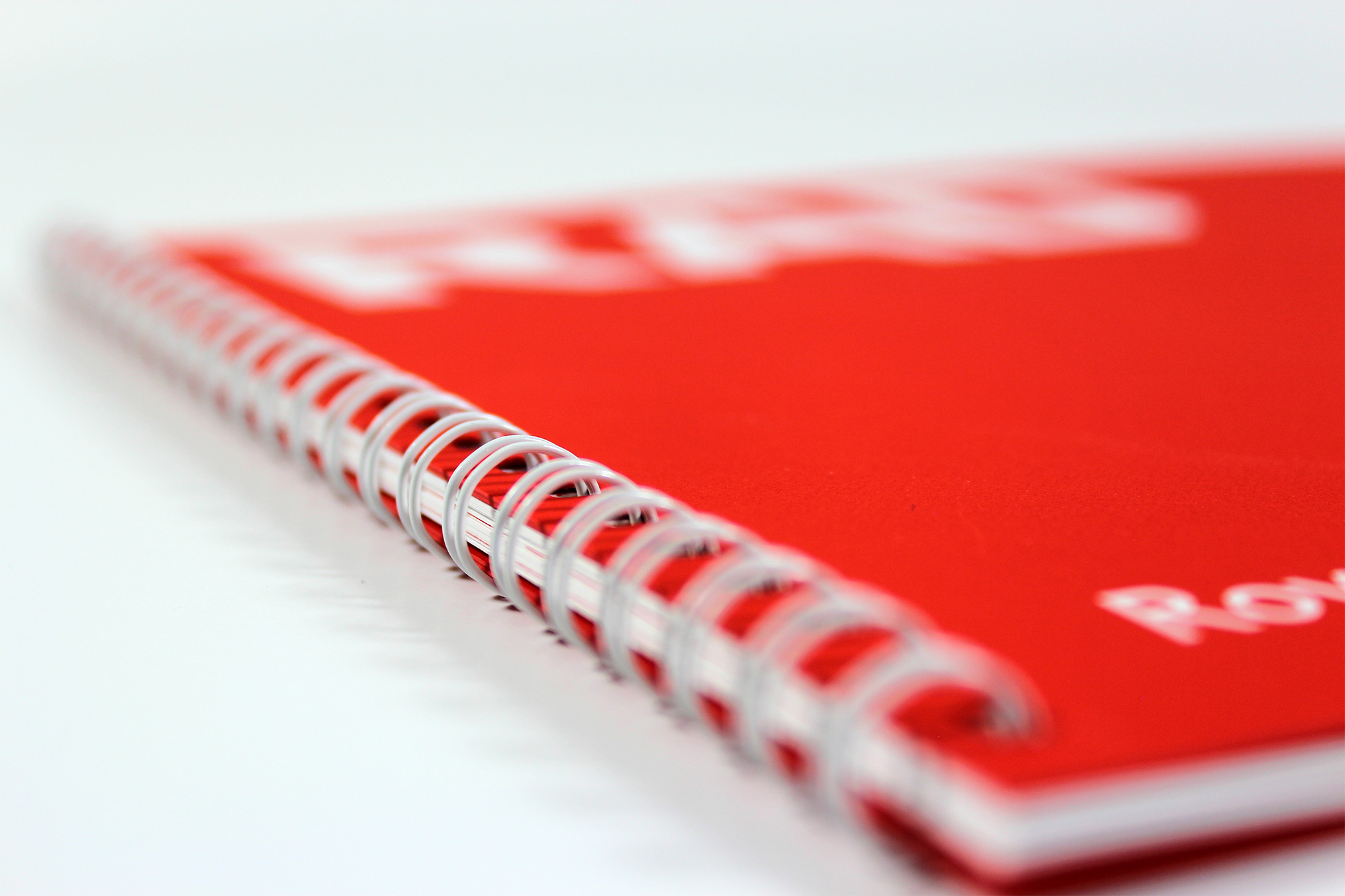 Printed Wiro-bound corporate promotional brochure for RAD - close-up showing the wiro-binding and red card front cover