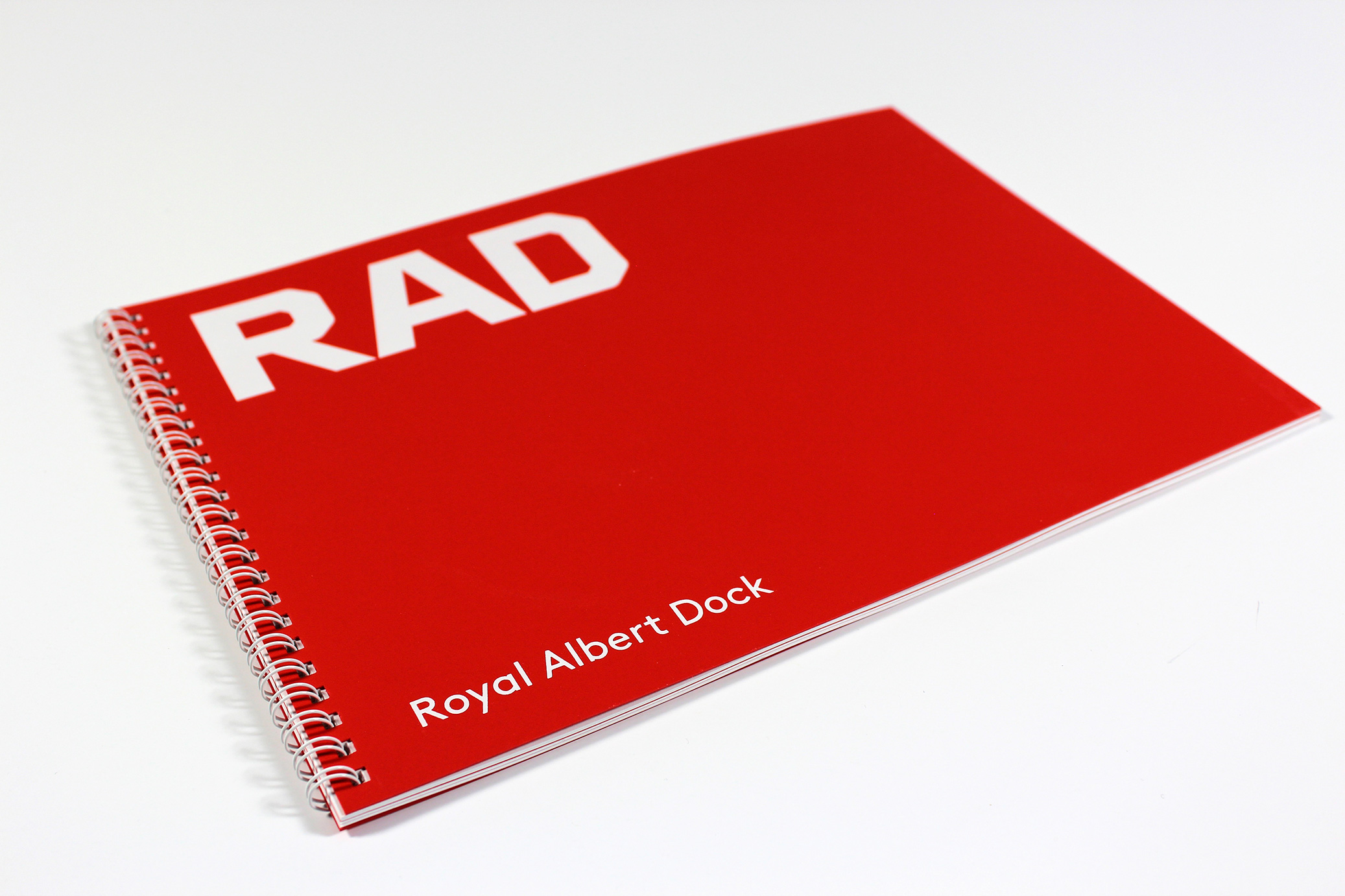 Printed Wiro-bound corporate promotional brochure for RAD - showing the binding and red card front cover