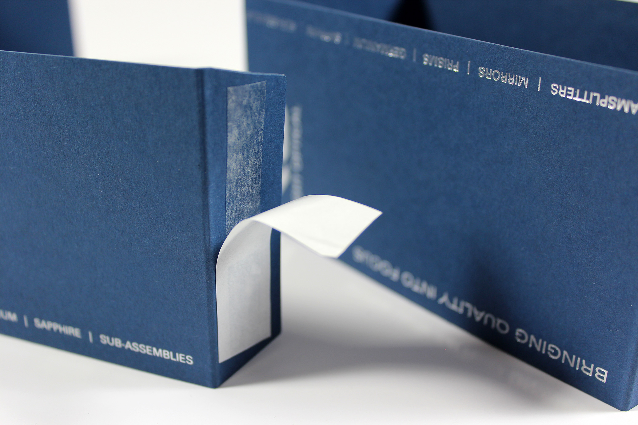 Silver foiled sleeve using blue card and taped on flap for Knight Optical - close-up of taped flap