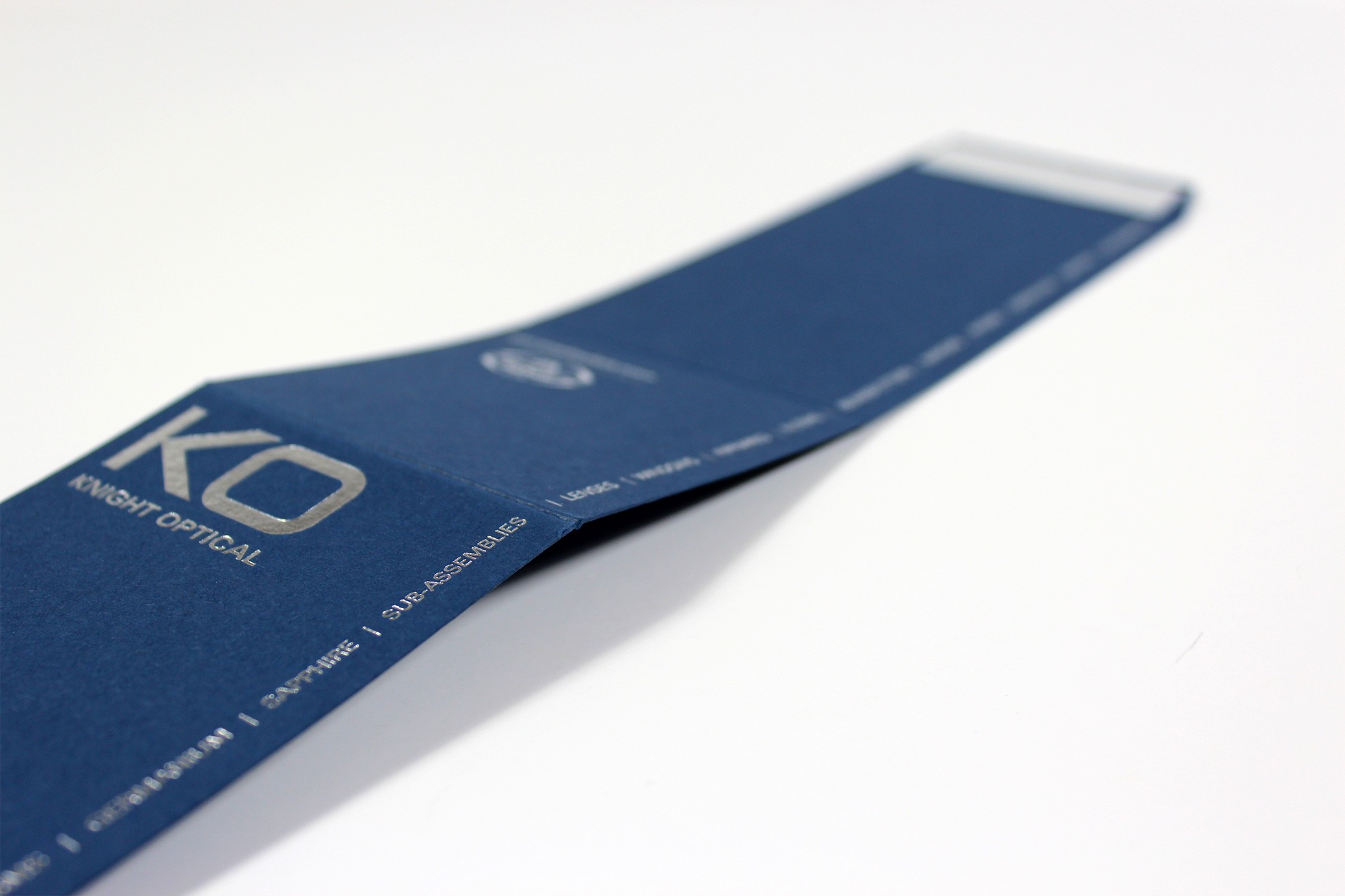 Silver foiled sleeve using blue card and taped on flap for Knight Optical - opened out flat