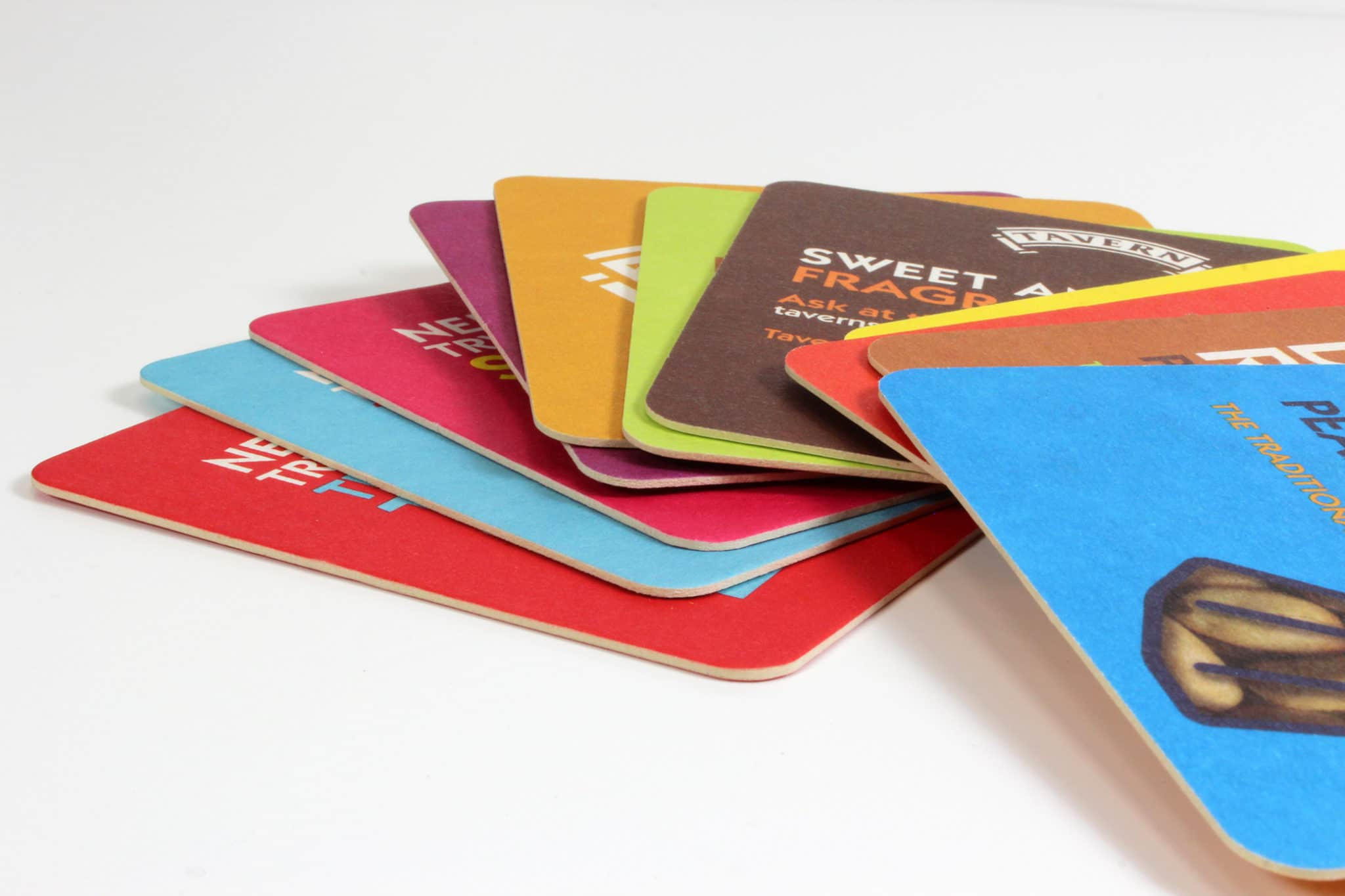 Colourful printed beer mats - different colours stacked on top of each other